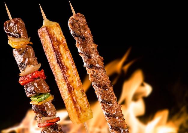 Geassorteerde biefstukspiesjes boven vuurvlammen.