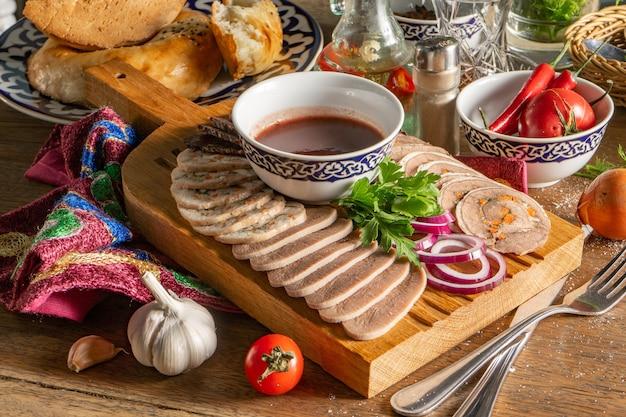 Geassorteerde broodjes kip, rundvlees, gekookte tong en balyk met tkemali-saus en rode ui, gesneden en geserveerd op een houten snijplank.