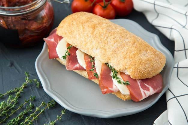 Geassorteerde broodjes. sandwich caprese met mozzarella en zongedroogde tomaten en ciabatta met ham