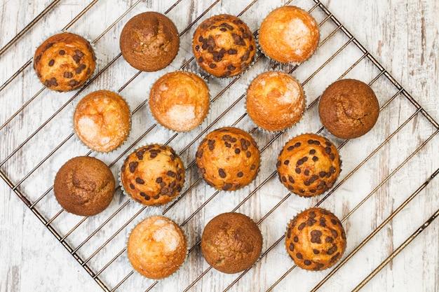 Geassorteerde cupcakes op een ovenrek en op een houten tafel