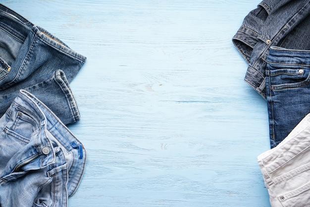 Geassorteerde denim broek op een blauwe houten tafel, plat leggen. plaats voor tekst.