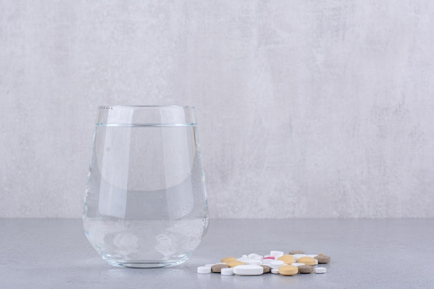 Geassorteerde farmaceutische geneeskundepillen en glas water. hoge kwaliteit foto