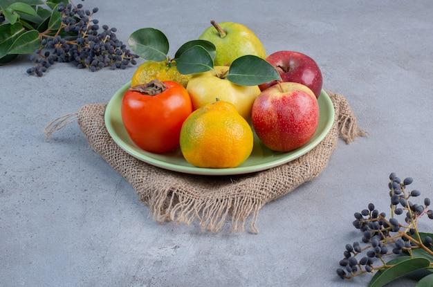 Geassorteerde fruitschotel op een stuk doek op marmeren achtergrond.