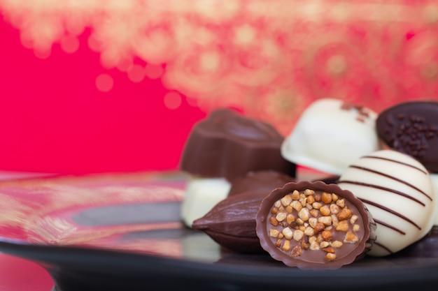 Geassorteerde gastronomische chocoladesuikergoed in verschillende vormen en kleuren in de schotel.