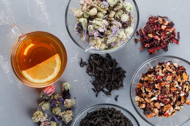 Geassorteerde gedroogde kruiden in glazen kommen met kopje thee plat op een gips oppervlak