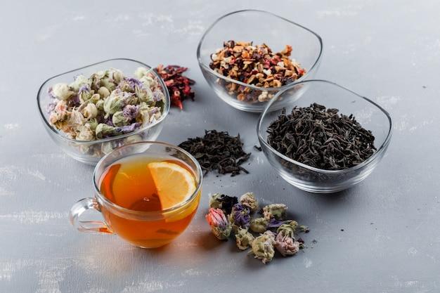 Geassorteerde gedroogde kruiden met kopje thee in glazen kommen op gips oppervlak