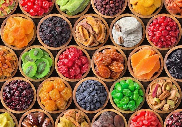 Geassorteerde gedroogde vruchten en bessen in houten kommen, bovenaanzicht. biologische voedsel achtergrond