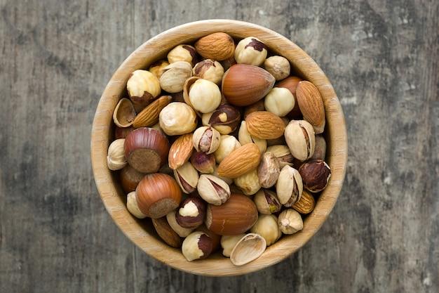 Geassorteerde gemengde noten in kom op houten tafel bovenaanzicht