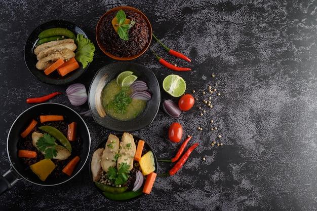 Geassorteerde gerechten en gerechten van groenten, vlees en vis op een zwarte stenen tafel. bovenaanzicht