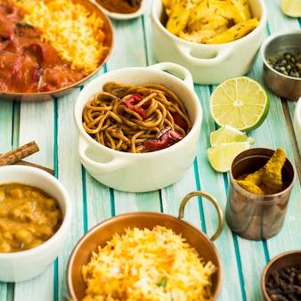 Geassorteerde gerechten en specerijen in de buurt van pasta en limoen