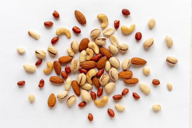 Geassorteerde geroosterde en ruwe noten die op wit worden verspreid