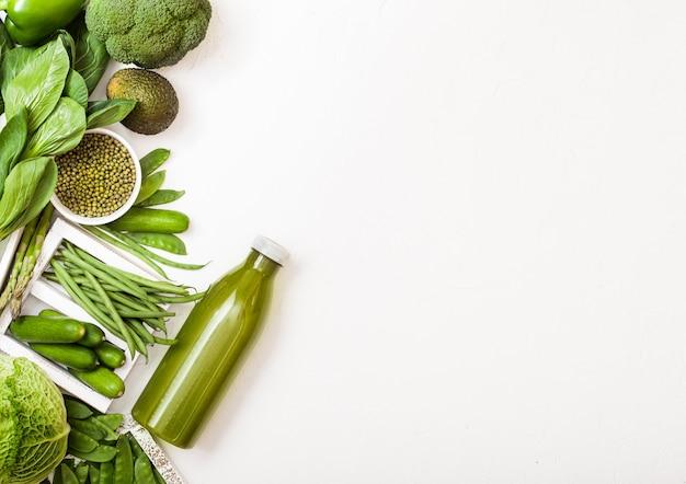 Geassorteerde groen afgezwakt rauwe biologische groenten op witte stenen oppervlak