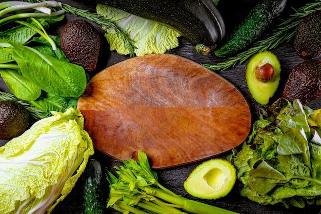 Geassorteerde groene groenten en snijplank, voedselachtergrond, exemplaarruimte.