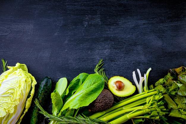 Geassorteerde groene groenten op zwarte achtergrond met exemplaarruimte.