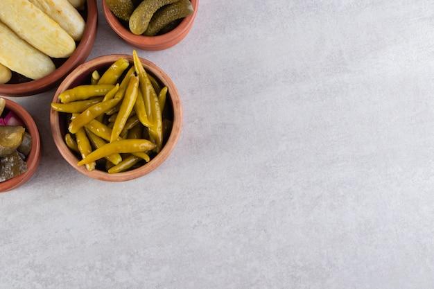 Geassorteerde groenten in het zuur die op een steenachtergrond worden geplaatst.