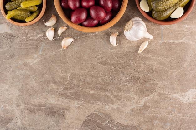 Geassorteerde groenten in het zuur in kommen die op stenen tafel worden geplaatst.