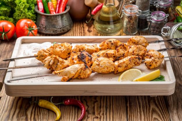 Geassorteerde heerlijk gegrild vlees met groente op de tafel van de witte plaatpicknick voor familiebbq partij