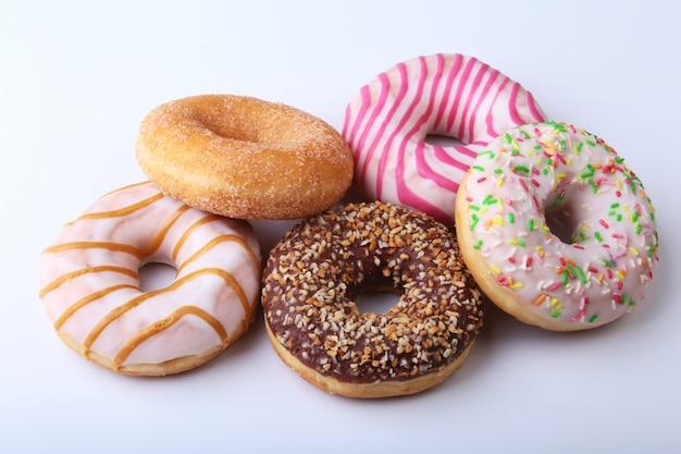 Geassorteerde heerlijke eigengemaakte donuts in het glazuur, kleurrijke hagelslag en noten geïsoleerd op een witte achtergrond.
