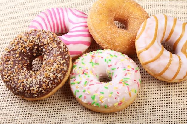 Geassorteerde heerlijke zelfgemaakte donuts in het glazuur, kleurrijke hagelslag en noten.