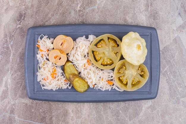 Geassorteerde ingemaakte groenten op een houten dienblad, op het marmer.