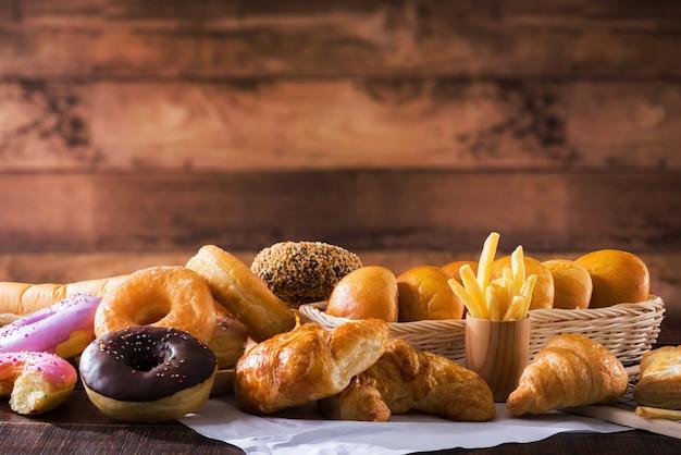 Geassorteerde junkfood meerdere soorten op houten tafel met kopie ruimte
