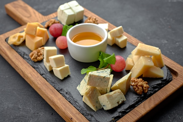 Geassorteerde kaas (kaasplank) op een zwarte tafel