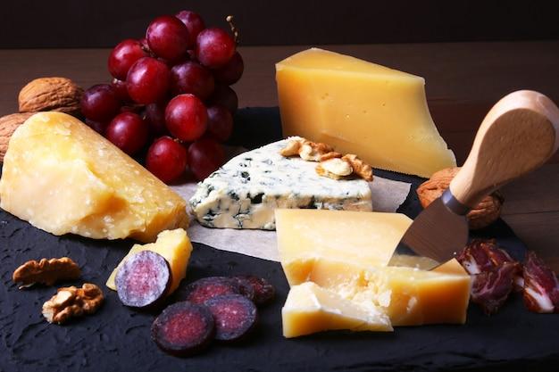Geassorteerde kazen, noten, druiven, fruit, gerookt vlees en een glas wijn op een serveertafel.