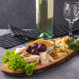 Geassorteerde kazen op een houten raadshoning, walnoten en druiven. lekkere kaasplaat.