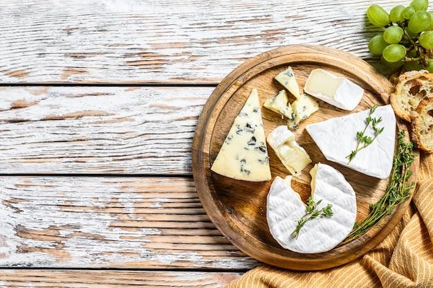 Geassorteerde kazen op een ronde houten snijplank. camembert, brie en blauwe kaas met druiven.