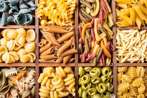 Geassorteerde kleurrijke italiaanse deegwaren in houten doos