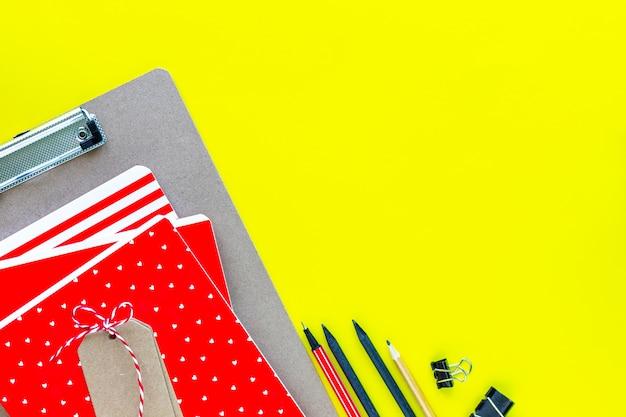 Geassorteerde kleurrijke kantoorbehoeften voor school en kantoor op gele achtergrond met copyspace.