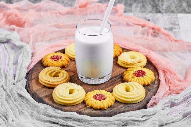 Geassorteerde koekjes en een pot melk op houten plaat met tafelkleden.