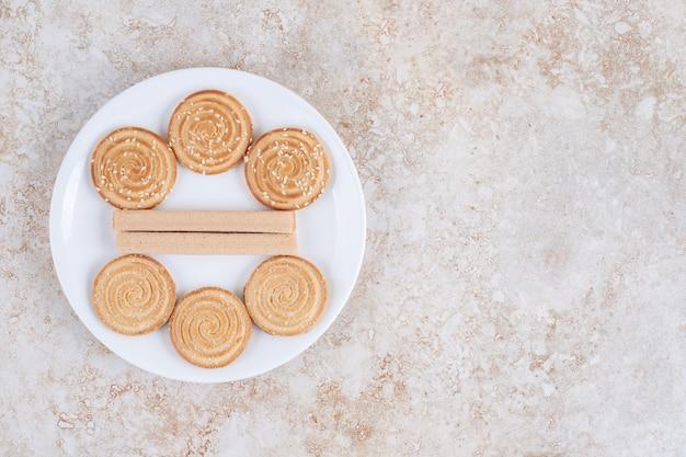 Geassorteerde koekjes op een bord, op de marmeren tafel.