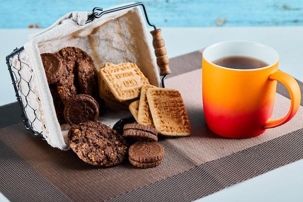 Geassorteerde koekjes, snoepjes en een kopje thee op een grijze ondergrond.