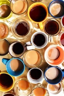 Geassorteerde koffiekopjes met koffie en op een tafel. bovenaanzicht