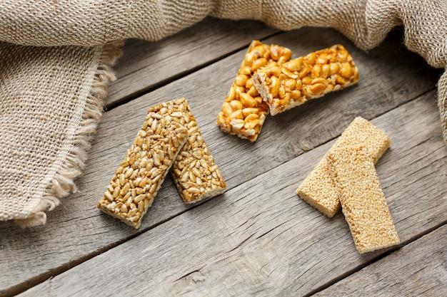 Geassorteerde kozinaki ,, met jute stof. landelijke stijl. heerlijke zoetigheden van de zaden van zonnebloem, sesam en pinda's, bedekt met glanzend glazuur.