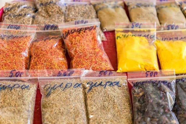 Geassorteerde kruiden en specerijen in doorzichtige plastic zakken op de markt