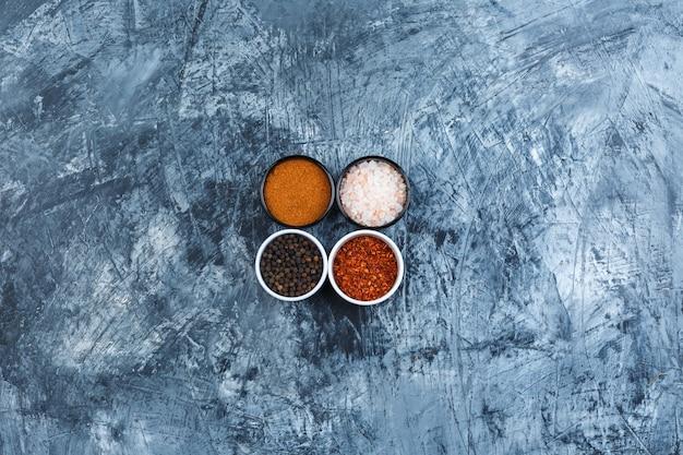 Geassorteerde kruiden in kleine kommen op een grijze gipsachtergrond. bovenaanzicht.