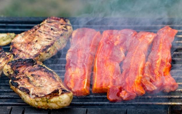 Geassorteerde mixed grill van kippenvlees en varkensvlees, worstjes roosteren op barbecue rooster gekookt voor zomer familiediner.