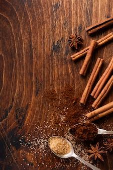 Geassorteerde natuurlijke kaneel, rietsuiker, gemalen koffie, anijsplantsterren die ingrediënten op een rustieke bruine lijst bakken.