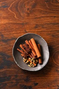 Geassorteerde natuurlijke pijpjes kaneel, kardemomkorrels, anijsplantsterren die ingrediënten op een rustieke bruine achtergrond bakken. natuurlijke kruiden.