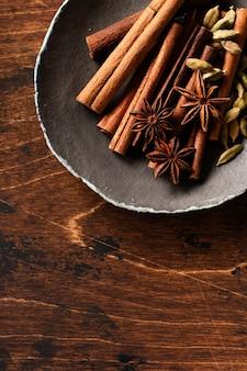Geassorteerde natuurlijke pijpjes kaneel, kardemomkorrels, anijsplantsterren die ingrediënten op een rustieke bruine lijst bakken. natuurlijke kruiden.
