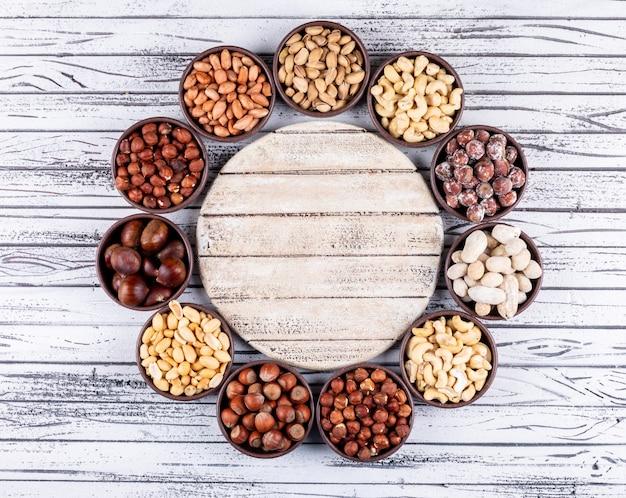 Geassorteerde noten en gedroogde vruchten in een cyclus vormige mini verschillende kommen met pecannoten, pistachenoten, amandel, pinda, close-up