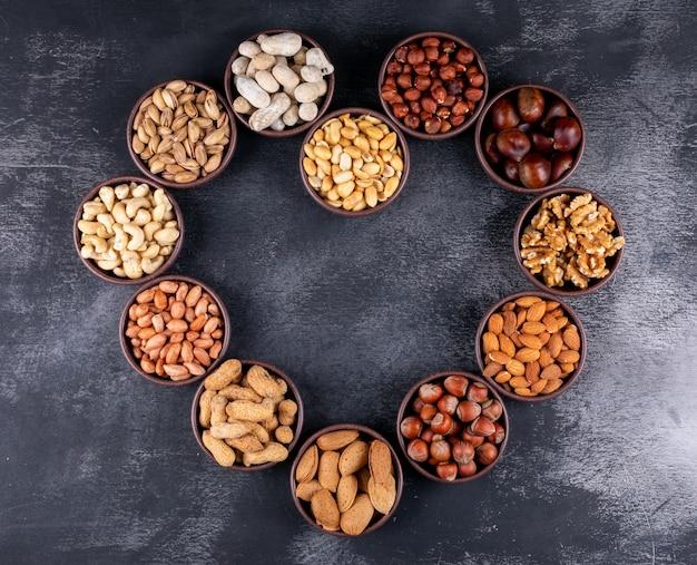 Geassorteerde noten en gedroogde vruchten in een hartvormige mini verschillende kommen met pecannoten, pistachenoten, amandel, pinda, bovenaanzicht