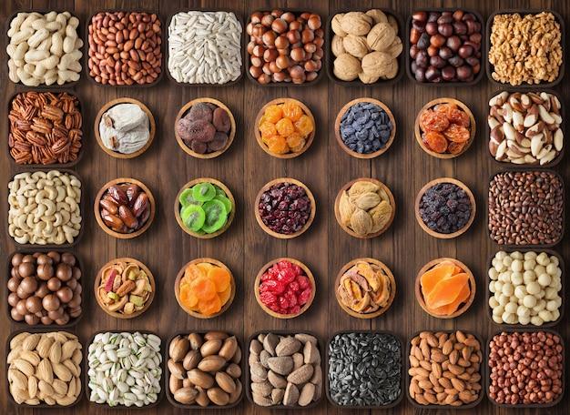 Geassorteerde noten en gedroogde vruchten op houten tafel, bovenaanzicht. gezonde snack in kommen, voedselachtergrond.