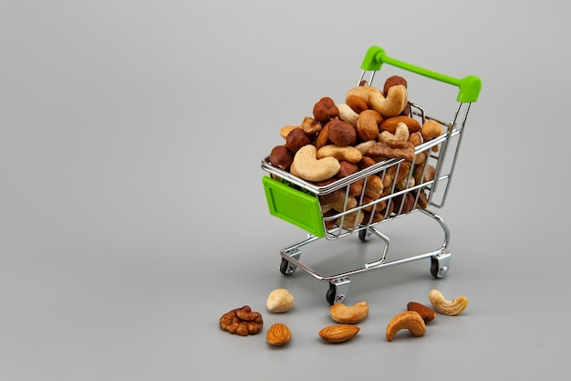 Geassorteerde noten in een apart marktmandje op een grijze achtergrond