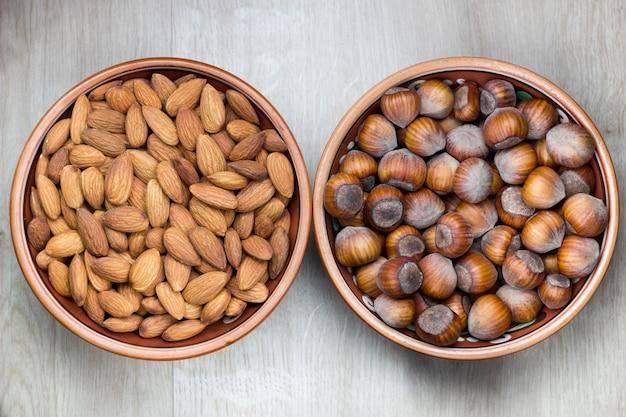 Geassorteerde noten in kommen op een witte houten achtergrond. ruimte kopiëren.