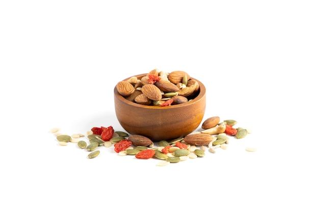 Geassorteerde noten worden in een bruine houten beker op een wit oppervlak geplaatst met amandelen, zonnebloempitten, meloenpitten, cashewnoten, gekruide kee.