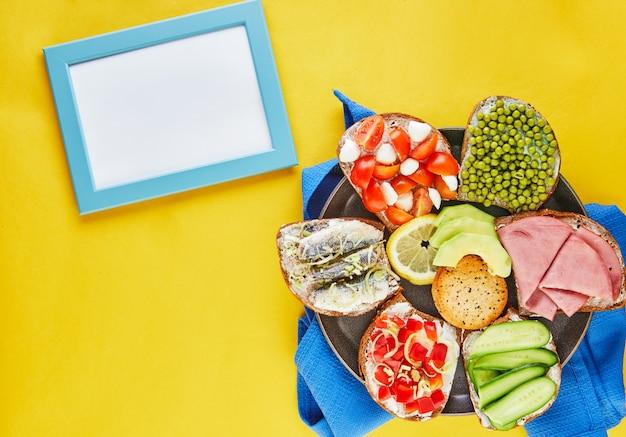 Geassorteerde open sandwiches, sandwiches met plakjes zuurdesem met verschillende vullingen op een bord met een blauw servet en een geel oppervlak bovenaanzicht. plat liggen. frame voor tekst - kopieer ruimte