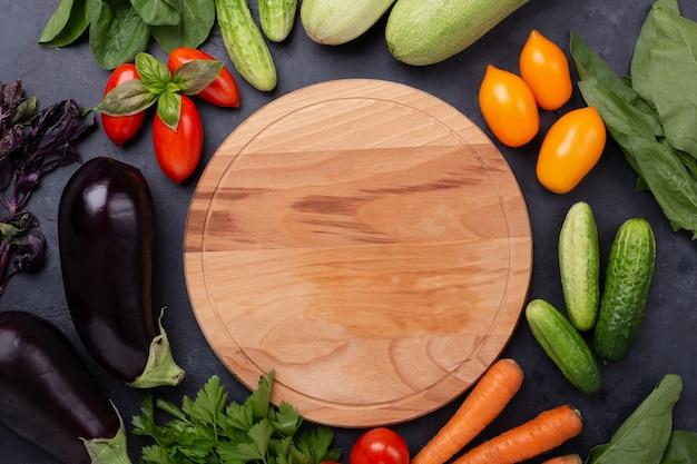 Geassorteerde rauwe biologische groenten en snijplank op donkere stenen achtergrond